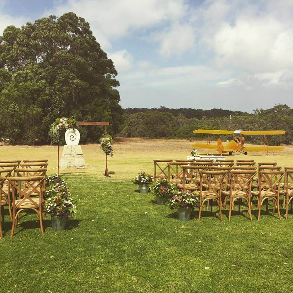 The wedding ceremony at Edwards Wines in Margaret River with our wooden crossback chairs, arbour and florals by Sorella Flower Merchant
